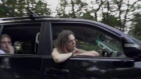 Το μαύρο αυτοκίνητο οδηγά αργά την οδική επιχείρηση τριών ανθρώπων ταξιδεύει τα ραβδιά κοριτσιών το κεφάλι της από το παράθυρο αυ φιλμ μικρού μήκους