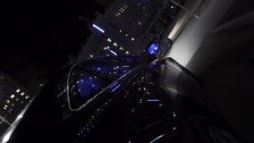 Το μαύρο αυτοκίνητο moder που κινείται στις οδούς πόλεων τη νύχτα με τα φω'τα των οδηγήσεων αυτοκινήτων λαμπυρίζει στα διαφορετικ φιλμ μικρού μήκους