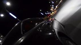 Το μαύρο αυτοκίνητο moder που κινείται στις οδούς πόλεων τη νύχτα με τα φω'τα των οδηγήσεων αυτοκινήτων λαμπυρίζει στα διαφορετικ απόθεμα βίντεο