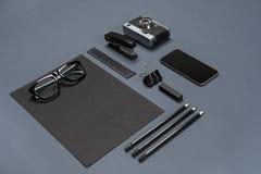 Το μαύρο επίπεδο συλλογής ουσίας γραφείων βρέθηκε Τοπ άποψη σχετικά με το σύνολο χαρτικών με το smartphone Στοκ Εικόνες