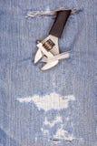 Το μαύρο εργαλείο λαβών πενσών διαπερνά μέσω του παλαιού τζιν παντελόνι backgroun Στοκ εικόνες με δικαίωμα ελεύθερης χρήσης