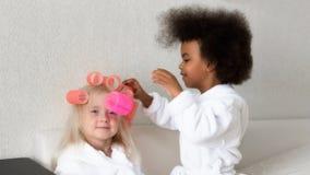 Το μαύρο κορίτσι κρεμά τα ρόλερ τρίχας στο φίλο της στοκ φωτογραφία