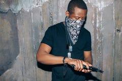 Το μαύρο μέλος συμμοριών ελέγχει το όπλο του Στοκ Φωτογραφίες