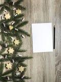 Το μαύρο μολύβι βρίσκεται δίπλα στο φύλλο και σε έναν ξύλινο πίνακα είναι κομψοί κλάδοι και marshmallows, μπισκότα πιπεροριζών Στοκ φωτογραφία με δικαίωμα ελεύθερης χρήσης