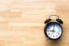 Το μαύρο ξυπνητήρι στο ξύλινο υπόβαθρο παρουσιάζει χρονική έννοια στοκ εικόνα