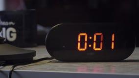 Το μαύρο ορθογώνιο διαμορφωμένο ηλεκτρονικό ψηφιακό ρολόι δείχνει το χρόνο στο πορτοκαλί χρώμα απόθεμα βίντεο