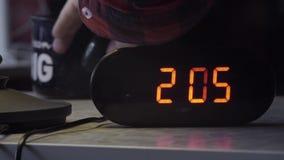 Το μαύρο ορθογώνιο διαμορφωμένο ηλεκτρονικό ψηφιακό ρολόι παρουσιάζει χρόνο στο πορτοκαλί χρώμα φιλμ μικρού μήκους