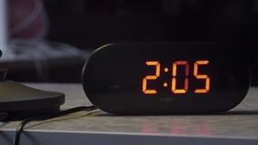 Το μαύρο ορθογώνιο διαμορφωμένο πλαστικό ψηφιακό ρολόι δείχνει το χρόνο στο πορτοκαλί χρώμα απόθεμα βίντεο