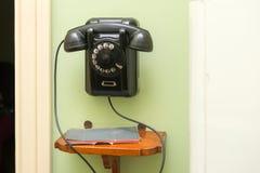 Το μαύρο παλαιό εκλεκτής ποιότητας τηλέφωνο κρεμά Στοκ φωτογραφία με δικαίωμα ελεύθερης χρήσης