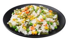 Το μαύρο πιάτο με το άσπρο ρύζι, πράσινα μπιζέλια, κονσερβοποίησε τους πυρήνες καλαμποκιού, πράσινα φασόλια περικοπών που απομονώ στοκ φωτογραφίες με δικαίωμα ελεύθερης χρήσης