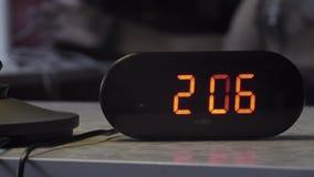Το μαύρο πλαστικό ηλεκτρονικό ψηφιακό ρολόι δείχνει το χρόνο στο πορτοκαλί χρώμα στον πίνακα απόθεμα βίντεο
