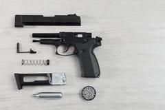 Το μαύρο πνευματικό πυροβόλο όπλο πιστολιών (αεροβόλο πιστόλι) διασκορπισμένο φωτίζει το BA Στοκ εικόνες με δικαίωμα ελεύθερης χρήσης