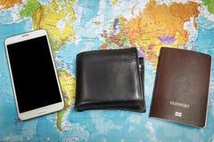 Το μαύρο πορτοφόλι και το διαβατήριο και το smartphone στον κόσμο χαρτογραφούν το υπόβαθρο για το ταξίδι σε όλο τον κόσμο Στοκ Φωτογραφία