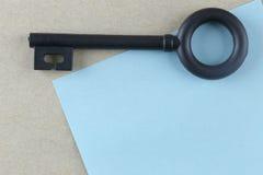 Το μαύρο πλαστικό κλειδί τοποθετείται στην μπλε σημείωση εγγράφου Στοκ Φωτογραφία