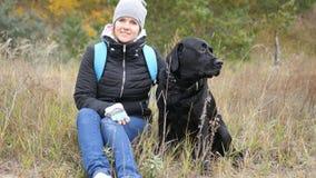 Το μαύρο σκυλί κάθεται δίπλα στην ιδιοκτήτρια του και φαίνεται ο άλλος τρόπος φωτογραφία στοκ εικόνες με δικαίωμα ελεύθερης χρήσης