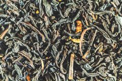 Το μαύρο τσάι, ξεραίνει τα φύλλα με τα λουλούδια για όλες τις φωτογραφίες ταπετσαρία στοκ εικόνες με δικαίωμα ελεύθερης χρήσης