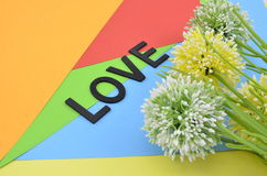 Το μαύρο χρώμα αγάπης λέξης στην κάθετη θέση το τεχνητό λουλούδι στο πορτοκαλί, κόκκινο, μπλε και πράσινο backgrou Στοκ Εικόνες