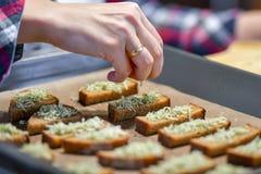 Το μαύρο ψωμί με το τυρί και τα καρυκεύματα, το κορίτσι ψεκάζει το τεμαχισμένο ψωμί στοκ εικόνα με δικαίωμα ελεύθερης χρήσης