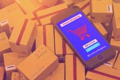 Το μαύρο smartphone τρέχει σε απευθείας σύνδεση αγορές app στη συσκευασία cardboar Στοκ Φωτογραφία
