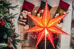 Το μεγάλο κόκκινο επτά έδειξε το αστέρι Χριστουγέννων στο χριστουγεννιάτικο δέντρο και την εστία στοκ εικόνα