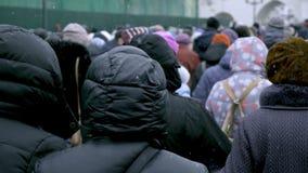 Το μεγάλο πλήθος των ανθρώπων περπατά κατά μήκος της οδού πόλεων Ο χειμώνας, χιόνι πέφτει φιλμ μικρού μήκους