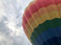 Το μεγάλο πολύχρωμο φωτεινό στρογγυλό ουράνιο τόξο χρωμάτισε το ριγωτό ριγωτό πετώντας μπαλόνι με ένα καλάθι ενάντια στον ουρανό  στοκ φωτογραφίες