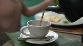 Το μεγάλο στενό επάνω σε αργή κίνηση τσάι χύνεται από τη μαύρη κατσαρόλα στο μεγάλο άσπρο φλυτζάνι φιλμ μικρού μήκους