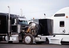 Το μεγάλο τρακτέρ φορτηγών εγκαταστάσεων γεώτρησης μαύρο ημι με την ανοικτή κουκούλα προετοιμάζει τη μηχανή τ Στοκ εικόνα με δικαίωμα ελεύθερης χρήσης