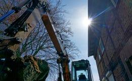 Το μεγάλο φτυάρι εκσκαφέων στο backlight γέμισε με ένα δυνατό φορτίο της χαλαρής καφετιάς άμμου στο εργοτάξιο οικοδομής Στοκ Εικόνες