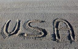 Το μεγάλο WORD ΗΠΑ Ηνωμένες Πολιτείες της Αμερικής στην άμμο Στοκ Φωτογραφία