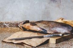 Το μεγάλο αποξηραμένο ψάρι βρίσκεται στον τέμνοντα πίνακα Επόμενο μαχαίρι Στοκ Εικόνες