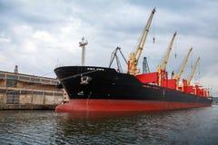 Το μεγάλο βιομηχανικό σκάφος με τους γερανούς φορτώνει στο λιμένα Στοκ εικόνες με δικαίωμα ελεύθερης χρήσης