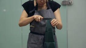 Το μεγάλο μαχαίρι ανθοκόμων κόβει τη μορφή κώνων ενός πράσινου floral σφουγγαριού φιλμ μικρού μήκους