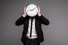 το μεγάλο ρολόι ανασκόπησης που καλύπτει το πρόσωπο γκρίζο η εκμετάλλευσή του απομόνωσε το άτομο πέρα από το λευκό κοστουμιών Στοκ εικόνες με δικαίωμα ελεύθερης χρήσης
