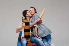 Το μεθυσμένο φίλημα ατόμων η σύζυγος, που κρατά την μπύρα πέρα από το γκρίζο υπόβαθρο Στοκ φωτογραφία με δικαίωμα ελεύθερης χρήσης
