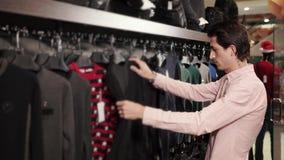 Το μελαχροινό μαλλιαρό άτομο φαίνεται ενδύματα στις κρεμάστρες στο καθιερώνον τη μόδα κατάστημα φιλμ μικρού μήκους