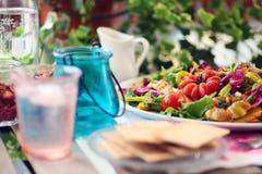 Το μεσημεριανό γεύμα με το ψημένο στη σχάρα κοτόπουλο, το μάγκο και η άνοιξη αναμιγνύουν τη σαλάτα στο μπαλκόνι στοκ εικόνα με δικαίωμα ελεύθερης χρήσης