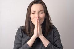 Το μετωπικό πορτρέτο κινηματογραφήσεων σε πρώτο πλάνο μιας γυναίκας την δίπλωσε παραδίδει το μέτωπο του προσώπου της, προσευχή, κ στοκ εικόνες