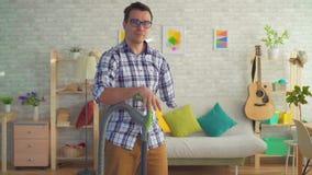 Το με ειδικές ανάγκες άτομο νεαρών άνδρων χωρίς ένα χέρι καθαρίζει το σπίτι με μια ηλεκτρική σκούπα και εξετάζει τη κάμερα φιλμ μικρού μήκους