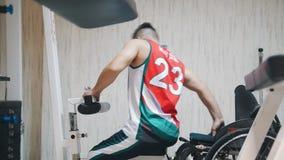 Το με ειδικές ανάγκες άτομο που σηκώνεται από να κάνει αναπηρικών καρεκλών ασκεί και να αναπνεύσει σκληρά εκπαιδευτικό στη γυμνασ φιλμ μικρού μήκους