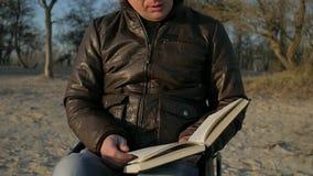 Το με ειδικές ανάγκες άτομο πορτρέτου, άτομα με ειδικές ανάγκες διαβάζει τη Βίβλο, αρσενικός άκυρος στη ρόδα απόθεμα βίντεο