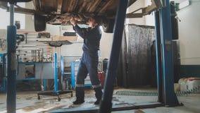 Το μηχανικό εργαστήριο γκαράζ - κατώτατο σημείο του αυτοκινήτου - ανύψωσε την αυτόματη στάση στην αυτοκινητική υπηρεσία στοκ φωτογραφία