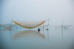 Το μη αναγνωρισμένο άτομο ψαράδων ελέγχει τα δίχτυα του στα ξημερώματα στον ποταμό σε Hoian, Βιετνάμ Στοκ φωτογραφία με δικαίωμα ελεύθερης χρήσης