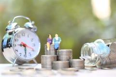 Το μικροσκοπικό ζεύγος που στέκεται στα χρήματα νομισμάτων και το μπουκάλι γυαλιού με το ρολόι alrm στο φυσικό πράσινο υπόβαθρο,  στοκ εικόνες με δικαίωμα ελεύθερης χρήσης
