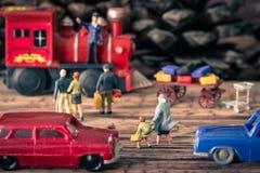 Το μικροσκοπικό παιχνίδι που περπατά πέρα από την οδό πηγαίνει στο ταξίδι με το τραίνο Στοκ Εικόνα