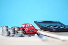 Το μικροσκοπικό πρότυπο αυτοκινήτων, νομίσματα συσσωρεύει, έγγραφο υπολογιστών και σημειωματάριων στον πίνακα γραφείων γραφείων Στοκ εικόνα με δικαίωμα ελεύθερης χρήσης