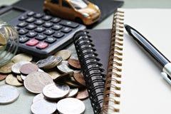 Το μικροσκοπικό πρότυπο αυτοκινήτων, υπολογιστής, νομίσματα διασκόρπισε από το βάζο γυαλιού, το έγγραφο σημειωματάριων και τη μάν Στοκ Εικόνες