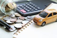 Το μικροσκοπικό πρότυπο αυτοκινήτων, υπολογιστής, νομίσματα διασκόρπισε από το βάζο γυαλιού, το έγγραφο σημειωματάριων και τη μάν Στοκ Φωτογραφίες
