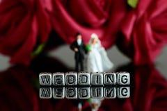 Το μικροσκοπικό πρότυπο γαμήλιο ζεύγος κλίμακας με το γάμο λέξης στις χάντρες και αυξήθηκε ανθοδέσμη Στοκ Εικόνες