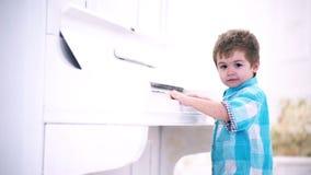 Το μικρό αγόρι απολαμβάνει το πιάνο, πρώτη φορά Στάση παιδιών κοντά στο πληκτρολόγιο πιάνων, άσπρο υπόβαθρο Το παιδί ξοδεύει τον  απόθεμα βίντεο